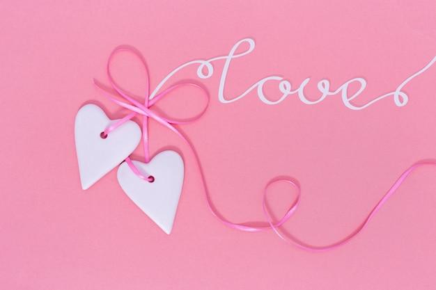 バレンタインデーの背景概念。コピースペースとピンクの紙の背景にリボンに2つの心がハングアップします。上面図。