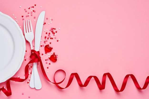 Valentines day background or concept with empty white plate, small heart-shaped plate with small hearts inside and whiteware on pink background. top view with copy space.