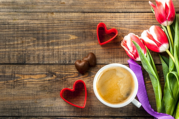 Valentines day background for congratulations, greeting cards. fresh spring tulips flowers with chocolate hearts candy and coffee mug and red hearts, on a wooden background top view copy space