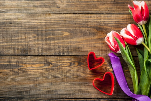 Valentines day background for congratulations, greeting cards. fresh spring tulips flowers with red hearts, on a wooden background top view copy space