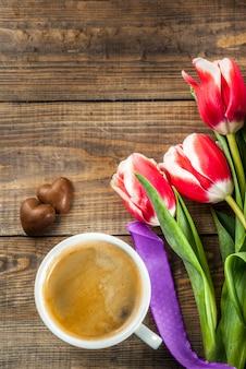 おめでとう、グリーティングカードのバレンタインデーの背景。チョコレートハートのキャンディとコーヒーのマグカップ、木製の背景上面コピースペースに新鮮な春のチューリップの花
