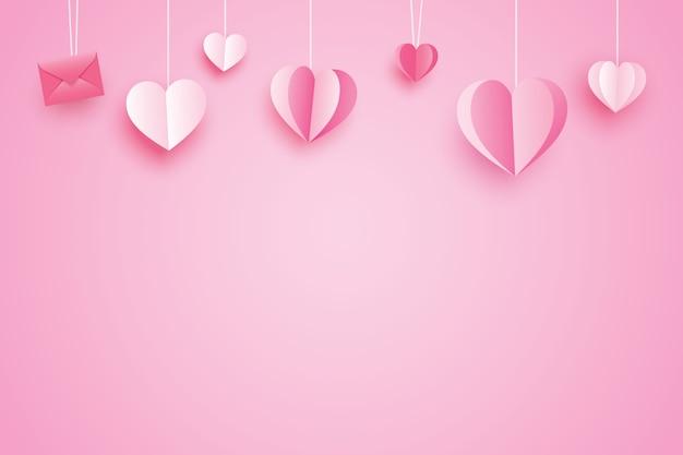 ピンクのパステルカラーに掛かっている紙のハートとグリーティングカードのバレンタインデーの背景。
