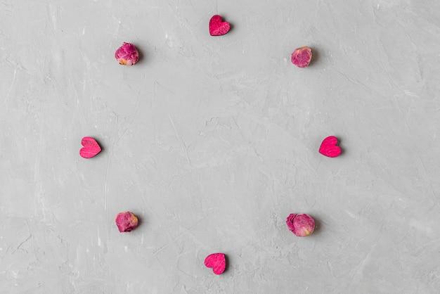 バレンタインデーの背景。灰色のコンクリートの背景に乾燥した牡丹の花と木製のハートで作られたフレーム。最小限のコンセプト。コピースペースのある上面図