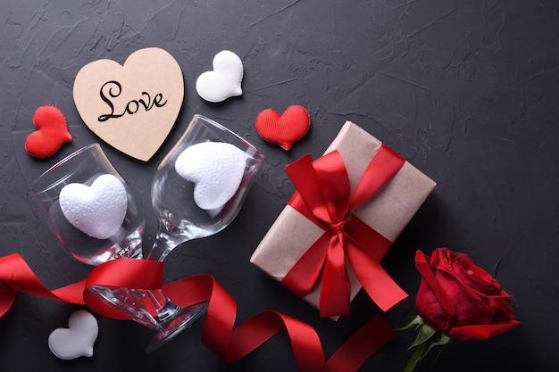 Символы влюбленности поздравительной открытки предпосылки дня валентинок, красное украшение с подарками роз сердца стекел на каменной таблице. вид сверху с копией пространства и текста. плоская планировка