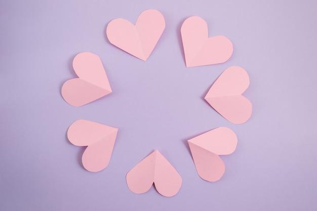 バレンタインデーの背景ハンドカットピンクのハートは円の中にあります