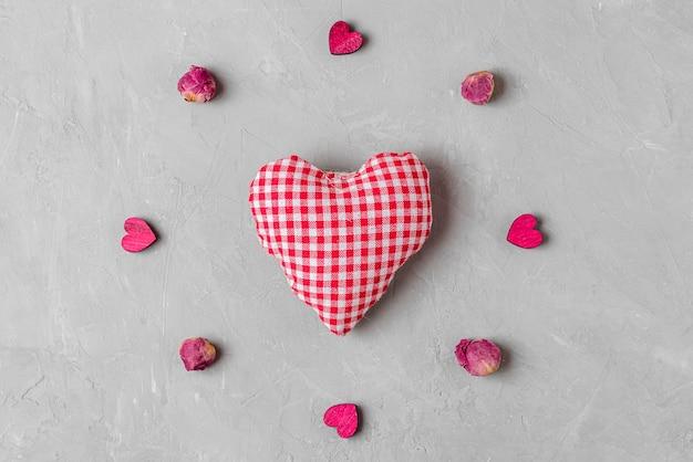 バレンタインデーの背景。灰色のコンクリートの背景に乾燥した牡丹の花と木製のハートで作られたフレームの手作りのテキスタイルハート。最小限のコンセプト。上面図