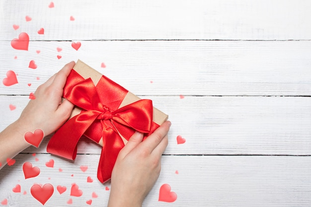 Valentines day background. hands hold a box with a gift and a red ribbon on a white wooden background