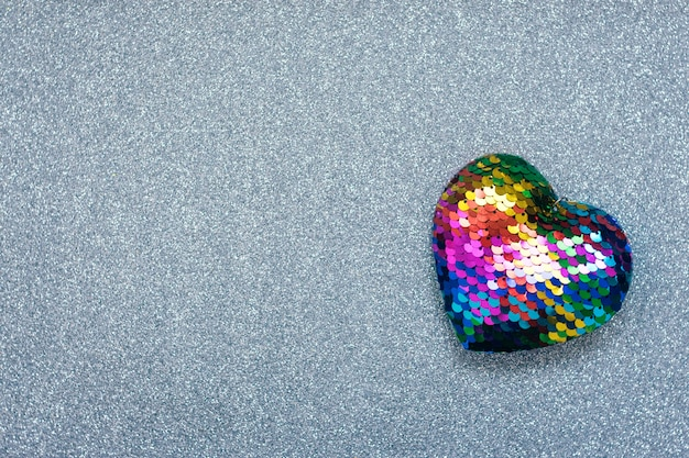 Valentines day background, mockup with one lgbt rainbow heart on silver shiny glitter background. valentine day, love, romance, dating concept, copy space