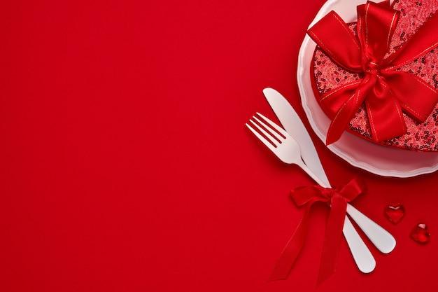 Предпосылка или концепция дня святого валентина с пустой розовой пластиной и белыми изделиями на алом или красном фоне. плоский вид сверху с копией пространства.