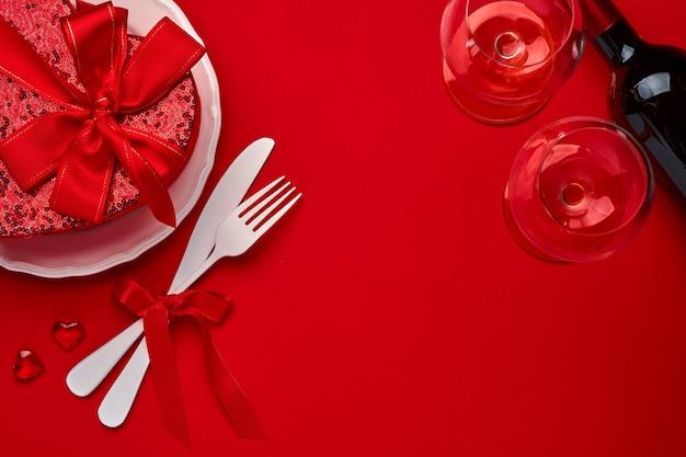 발렌타인 데이 배경 또는 개념에는 빈 흰색 접시와 칼 붙이 포크와 칼, 샴페인, 안경, 주홍색 또는 빨간색 배경에 선물 상자가 있습니다. 복사 공간이 있는 평면도 평면도.