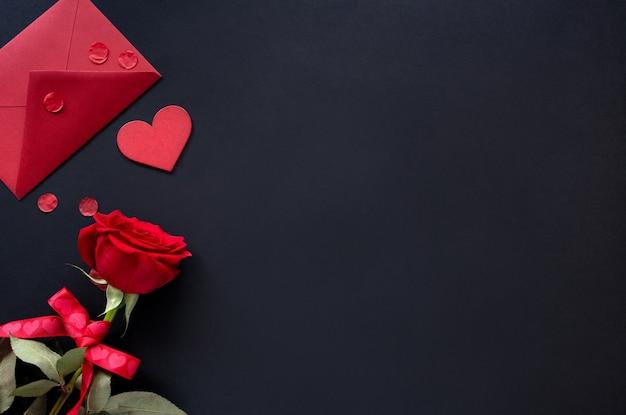 День святого валентина фон. красные цветы розы и конверт с сердцем на черном фоне, вид сверху, копией пространства