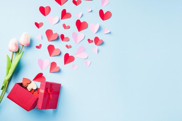 День святого валентина фон. красная подарочная коробка, открытка и бумажные летающие элементы, сердечки, вырезанные из поздравительной подарочной карты