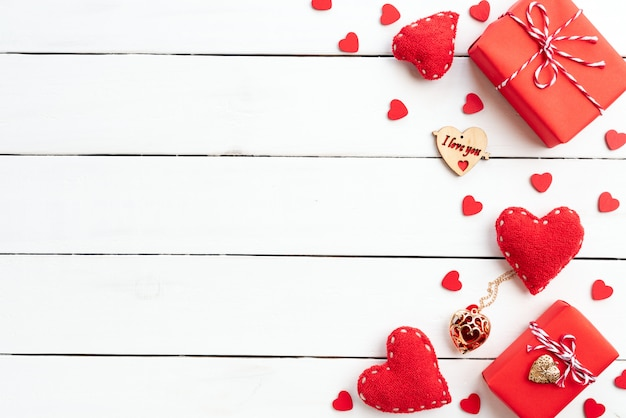 Valentines day background, red gift box with red heart on wooden background.