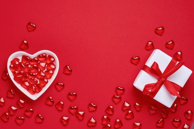 バレンタインデーの背景。小さなハートが入った小さなハート型のプレートと赤いリボンが付いた白いギフトボックス。上面図。