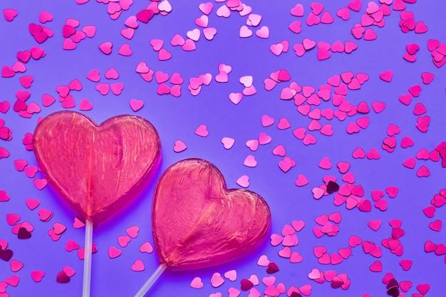 발렌타인 데이 배경. 보라색 배경에 반짝이와 두 사탕 마음. 평면도, 복사 공간