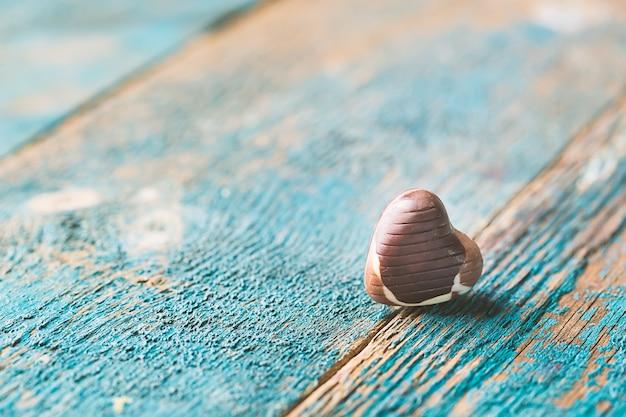青い木製のテーブルの上のチョコレート菓子の心とバレンタインデーの背景