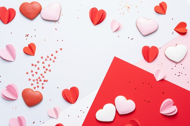 Valentines day background with cookies, red and pink hearts on pastel background