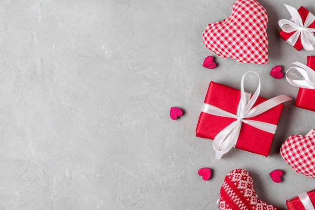 灰色のコンクリートの背景にギフトボックスとハートのバレンタインデーの背景。最小限のコンセプト。フラットレイ。コピースペースのある上面図