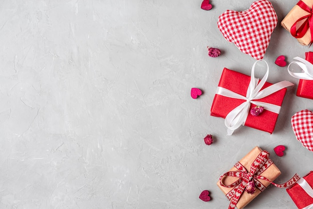 バレンタインデーの背景にギフトボックス、ファブリックのハート、灰色のコンクリートの背景にドライフラワー。フラットレイ。コピースペースのある上面図
