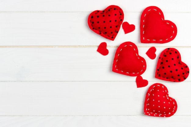 Valentines day background with handmade toy hearts on wooden table