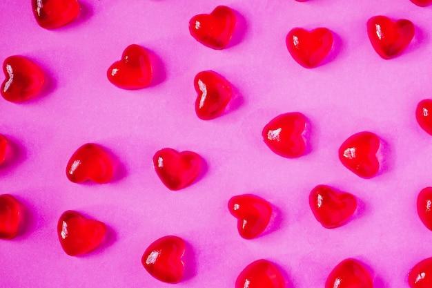 ピンクの背景にハート型キャンディーとバレンタインデーの背景