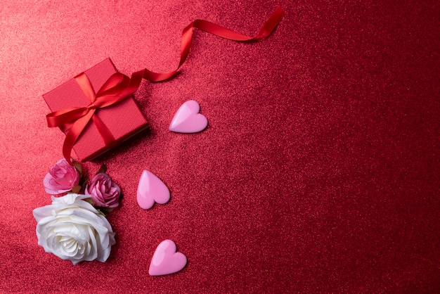 Valentines day background with pink hearts and gift on red copy space background.