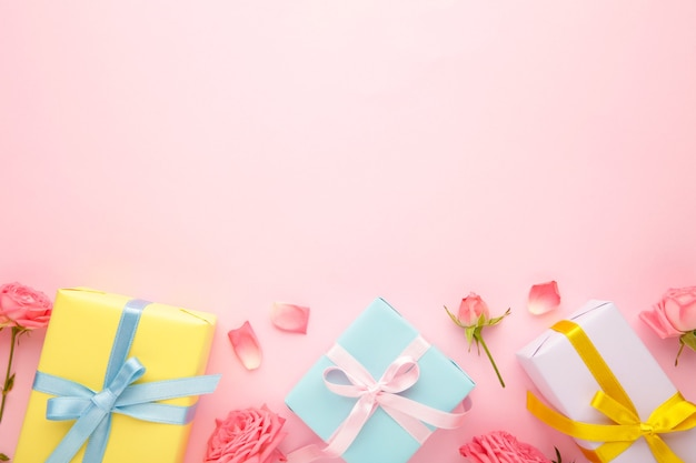 ピンクのバラとピンクの背景にギフトボックスとバレンタインデーの背景。コピースペースのある上面図。