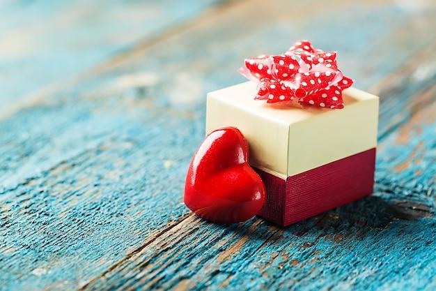 赤いハートと青い木製のテーブルの上のギフトボックスとバレンタインデーの背景