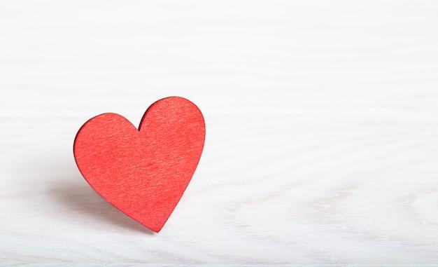 木製のテーブルに赤いハートとバレンタインデーの背景。コピースペース