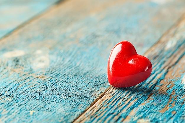 青い木製のテーブルの上の赤いハートとバレンタインデーの背景