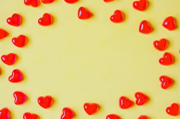 노란색 바탕에 붉은 심장 모양 사탕과 발렌타인 데이 배경