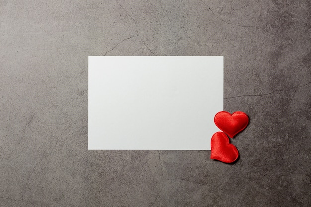 Valentines day background with red hearts and a blank paper on old concrete table.