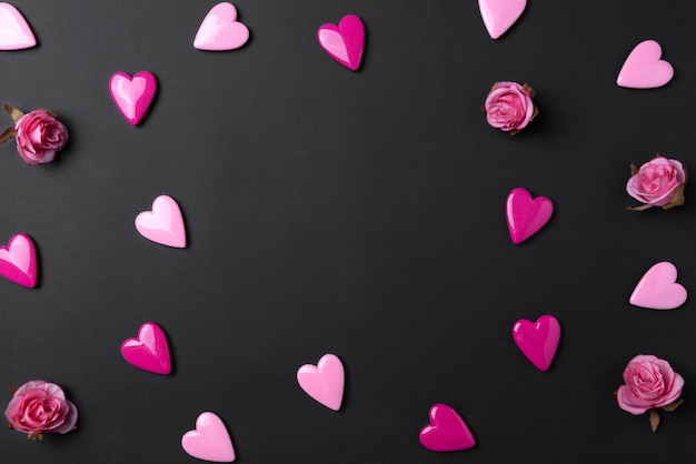 Valentines day background with red hearts and rose on black copy space background.