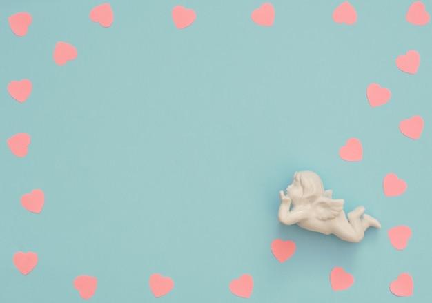 白いキューピッドとピンクの紙の心とバレンタインデーの背景