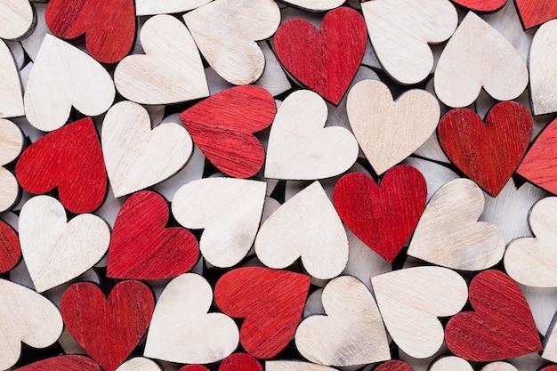 木製のテーブルの上の白い端の赤いハートとバレンタインデーの背景。