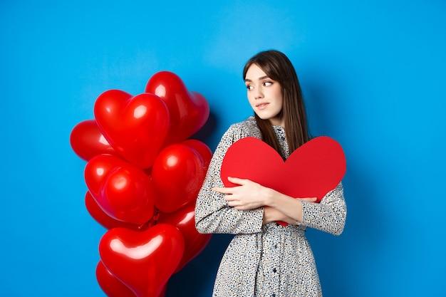 День святого валентина красивая и романтичная женщина задумчиво смотрит на воздушные шары, обнимая большое красное сердце и см ...