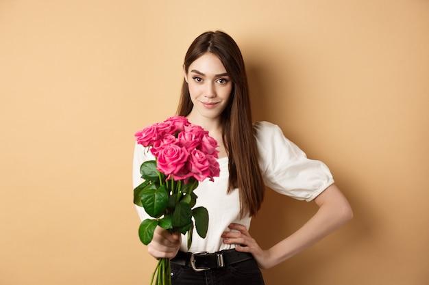 ピンクのバラを持ってカメラを見て若い女性がfloを受け取るバレンタインデーの美しいガールフレンド...
