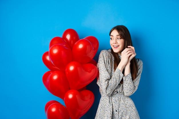 San valentino. bella ragazza romantica che sogna fuori appuntamento, in piedi vicino a palloncini cuore adorabili e sorridente, sfondo blu.