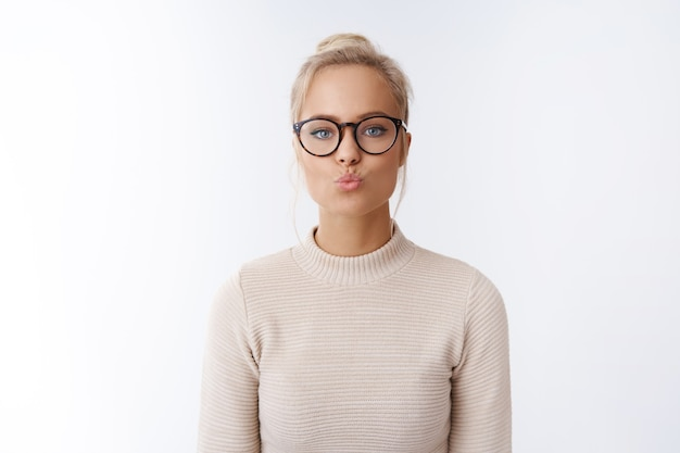 Valentines day, beauty and lifestyle concept. playful and fllirty good-looking young european female in glasses folding lips sending air kiss being romantic showing mwah sympathy over white wall