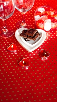 Valentines day. black chocolate in a heart shaped plate on red background. love dinner concept - vertical photo