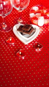 バレンタイン・デー。赤い背景の上のハート型のプレートにブラックチョコレート。愛の夕食の概念-垂直写真