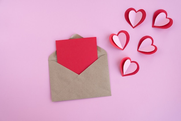 Valentines day. blank card with envelope and hearts on pink surface