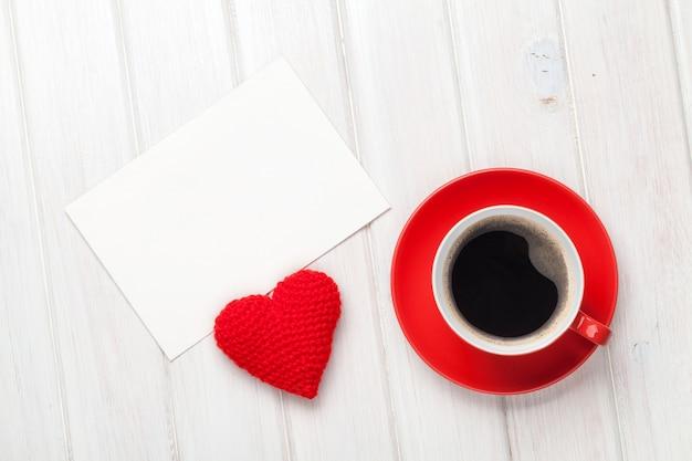 バレンタインデーの空白のグリーティングカード、コーヒーカップ、白い木製のテーブルの上のハート型のおもちゃ
