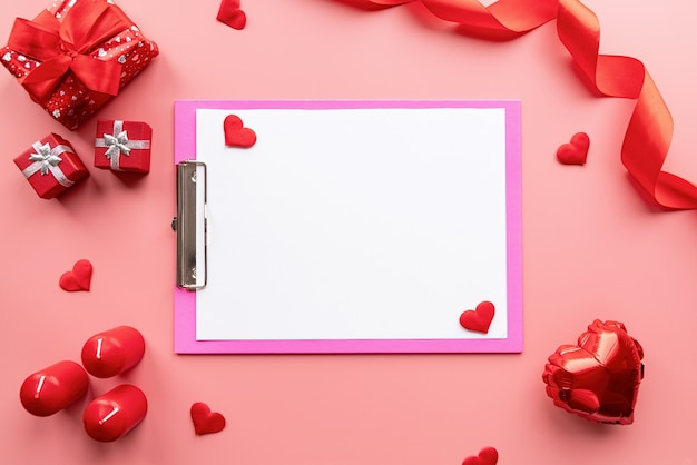 Valentines day. blank paper on pink clipboard with valentine decorations candles, balloons and confetti