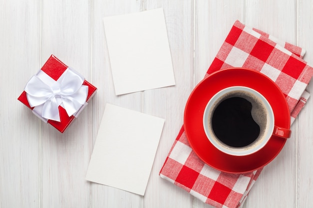 バレンタインデーの空白のフォトフレーム、コーヒーカップ、白い木製のテーブルの上のギフトボックス