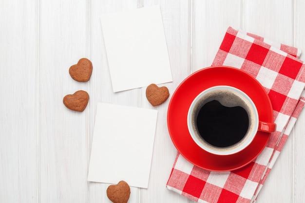 バレンタインデーの空白のフォトフレーム、コーヒーカップ、白い木製のテーブルの上のハート型のクッキー