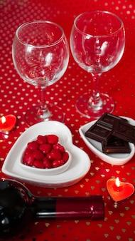 バレンタイン・デー。つるのボトル、グラス、赤いバラ、キャンドル-赤い背景。愛の夕食の概念-垂直写真
