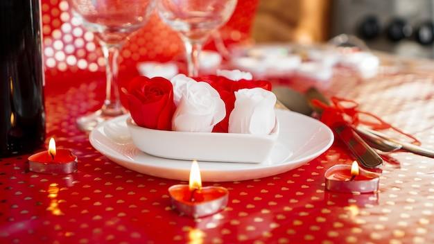 バレンタイン・デー。つるのボトル、グラス、赤いバラ、キャンドル-赤い背景。ディナーのコンセプトが大好き