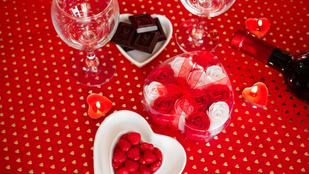Valentines day. bottle of vine, glasses, red roses, candles - red background. love dinner concept