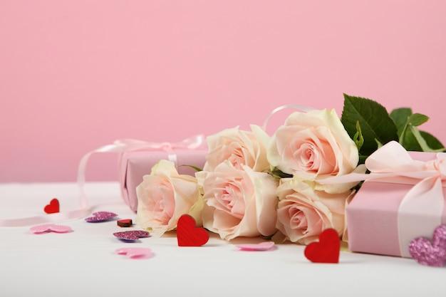 Букет на день святого валентина и подарки на розовом фоне